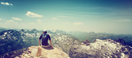 snow capped mountain: Mountain climber sitting on the edge of a rock facing away from the camera admiring the view at the summit of an alpine peak as he looks out across snow capped mountain ranges Stock Photo