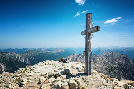 allgau: Summit Cross on High Mountain Top in Allgau Alps on Sunny Day with Blue Sky with Overview of Mountain Ranges in Distance, Near Germany-Austria Border