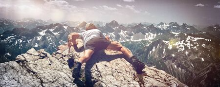 scrambling: Panoramic View of Man Scrambling Over Rocks on Mountain Ledge in Allgau Alps near German-Austrian Border