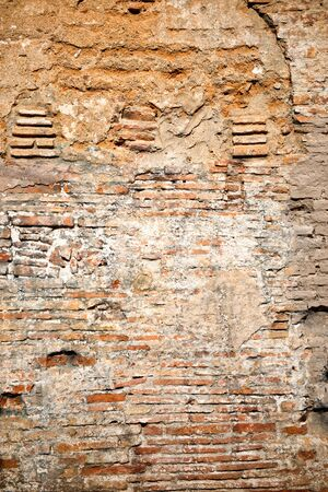 historical building: Ancient weathered brick wall background texture with exposed red clay bricks and missing plaster on a historical building Stock Photo