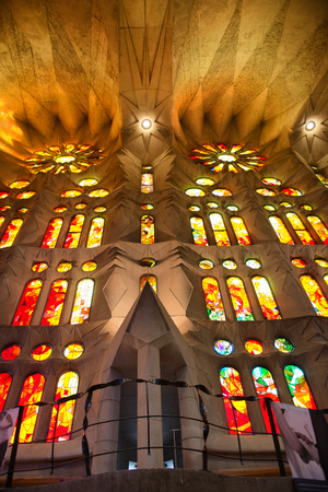 sagrada familia: Architectural Interior View of Sagrada Familia Church in Barcelona, Spain - Looking Up at Colorful Stained Glass Glowing in Exterior Sunlight