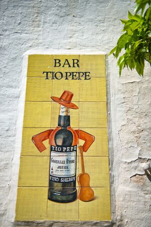Tiled artwork of an old bar or pub sign on a rough rendered white wall depicting a bottle of alcohol with a hat and guitar in Espanyol Poble, Barcelona, Spain