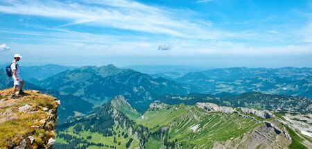 Hiker Standing on Outcrop Admiring View of Alpine Mountain Range and Lush Green Valley on Bright Sunny Day with Blue Sky