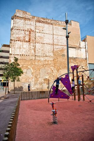 climbing frames: Children Playing on Playground in Fenced Area Across from Old Crumbling Building, Barcelona, Spain