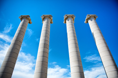 The Four Columns, ionic architectural vestige and tourist attraction, shot from low-angle under a blue sky with white clouds, in Barcelona, Catalonia, Spain Banco de Imagens