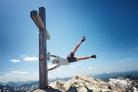 top mountain: Humorous Image of Man Clinging to Summit Cross on Extremely Windy Day in Allgau Alps with View of Mountains in Background, on Sunny Day with Blue Sky