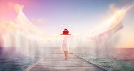 움직임을 나타내는 후광과 펼쳐진 날개와 흰 드레스에 바다 부두에 맨발로 서있는 여성의 천사의 영적 개념적 이미지는 미묘한 다채로운 태양 플레어