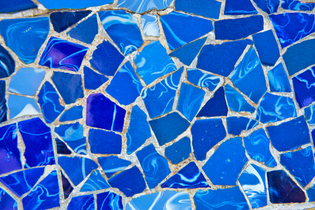Detail of bright blue ceramic mosaics on the curving wall on the main terrace, Parc Guell, Barcelona, Spain, designed by architect Antoni Gaudi and a Unesco world Heritage Site Редакционное