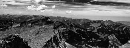 unspoilt: Black and White Panoramic Scenic View of Expansive Alpine Mountain Range with Dramatic Clouds