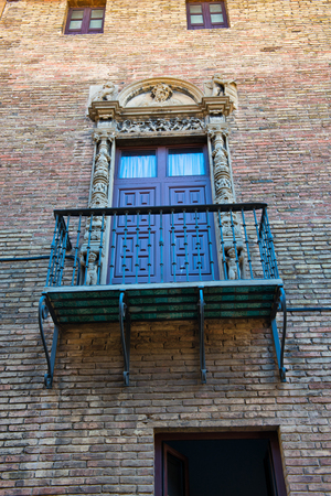 decorative balconies: Low Angle View of Balcony with Ornate Railing and Doorway on Exterior of Brick Building Wall, Barcelona, Spain Stock Photo