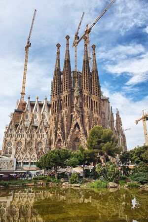 barcelona cathedral: Scenic view of the Sagrada Familia, Barcelona, Spain framed by shrubs, a church designed by Antoni Gaudi and popular tourist attraction
