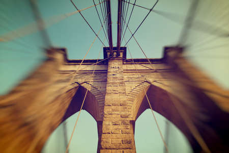 obscuring: Detail of the stonework of one of the towers on Brooklyn Bridge with a blur vignette obscuring the side suspension cables giving selective focus of the center column