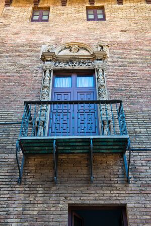 architrave: Low Angle View of Balcony with Ornate Railing and Doorway on Exterior of Brick Building Wall, Barcelona, Spain Stock Photo