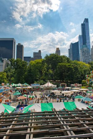 city park skyline: Fun fair with tents and stalls with crowds of people in Central Park, New York City, USA with skyscrapers visible on the skyline behind
