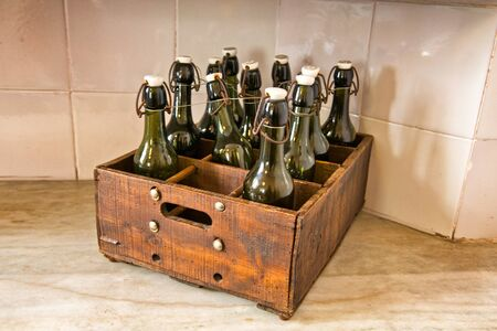 corked: Case of Old Fashioned Bottles in Wooden Box on Counter in Kitchen of Casa Mila, Barcelona, Spain