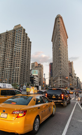 broadway tower: Traffic on 5th Ave, New York with traditional yellow taxi cabs approaching the Flatiron building in the background