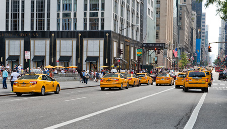 Iconic yellow taxi cabs on 5th Avenue, New York, viewed driving away from the rear in a busy street scene in the city