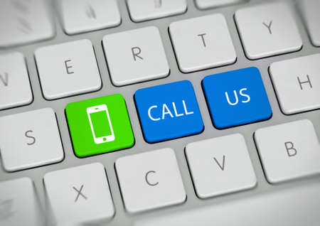 verbal: Call Us with green contact button in an online communication concept with the words - Call Us - on two blue keys on a white computer keyboard alongside a green mobile phone icon, viewed from above