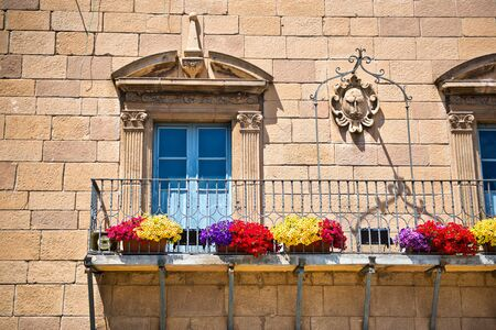 flower boxes: Stone townhouse with Art Nouveau windows with carved architraves above colorful flower boxes attached to the iron railing on the exterior balcony, Poble Espanyol, Barcelona, Spain