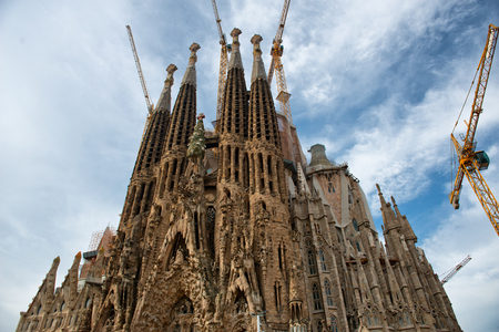 Street level view of the Sagrada Familia, Barcelona, Spain with tourists queueing to enter this popular tourist attraction Editorial
