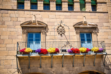 architrave: Stone townhouse with colorful flower boxes attached to the iron railing on the exterior balcony below Art Nouveau style windows with carved architraves, Poble Espanyol, Barcelona, Spain Stock Photo