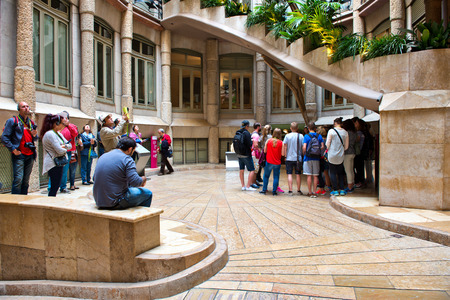 tourists: Groups of Tourists on Tour of Casa Mila Standing in Exterior Courtyard, Barcelona, Spain