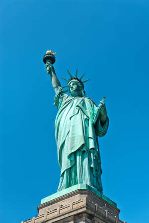 holding aloft: Low angle close up view of the iconic copper covered Statue of Liberty at the entrance to New York harbour holding aloft her torch against a clear blue sky in a tourism and travel concept
