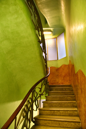stairwell: Stairwell with Ornate Railing Painted in Bright Lime Green Illuminated in Warm Light, Casa Mila, Barcelona, Spain