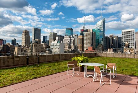 garden city: Rooftop patio in New York City with a table and chairs standing on a paved area surrounded by green turf overlooking a view of the downtown skyline and skyscrapers