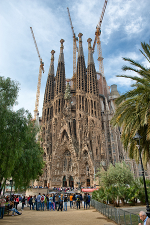 sagrada familia: External facade Sagrada Familia, Barcelona, Spain with a throng of tourists in the street waiting to enter the church designed by Antoni Gaudi Editorial