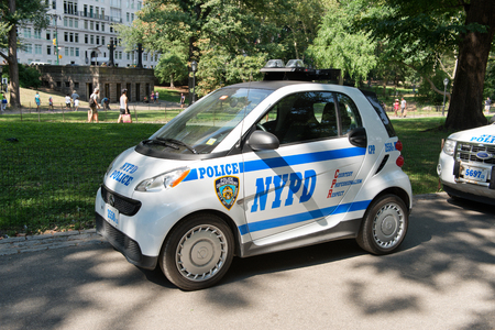 patrol car: Quaint little NYPD smart car parked in the shade of some trees with the NYPD insignia for a patrol car emblazoned on the side