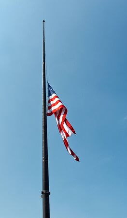 important event: United States national flag, the Stars and Stripes or Old Glory, flying at half mast to commemorate an important event or death against a blue sky