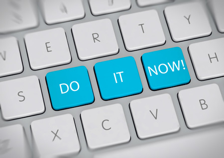 promptly: Do It Now concept with the words in white text on colorful turquoise blue keys on a white computer keyboard viewed high angle - Do not delay, do not procrastinate Stock Photo