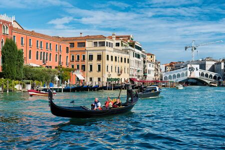 rialto: Tourists on a gondola on the Grand Canal in Venice with the Rialto bridge in the background in a travel and tourism concept