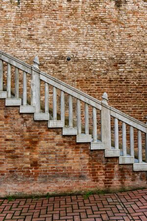 old city: Old exterior staircase on a historic red brick building leading up from an inner paved courtyard Stock Photo