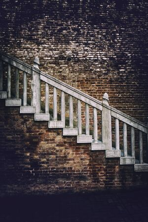 vignetting: Old external staircase on a red brick building with heavy vignetting around the sides and an ominous ambiance, highlight to the centre on the steps