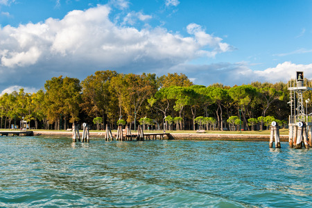 a memorial to fallen soldiers: Scenic View of Dock and Shoreline in Rimembranze Park with Lush Green Forest and Blue Sky, Island of Sant Elena, Venice, Italy
