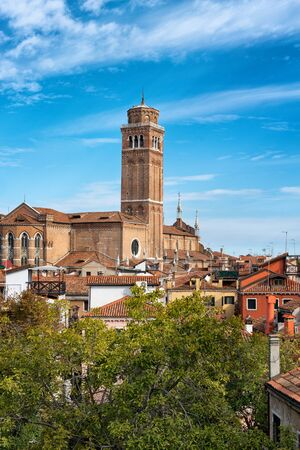 dominating: Skyline view of the Basilica dei Frari, Venice, Italy with its square campanile dominating the surrounding rooftops against a sunny blue sky