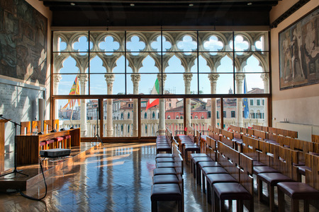 """Historic lecture hall """"Aula Baratto"""" in Ca Foscari University, Venice, Italy with a view through tall Gothic windows over the Grand Canal and its historical palaces"""