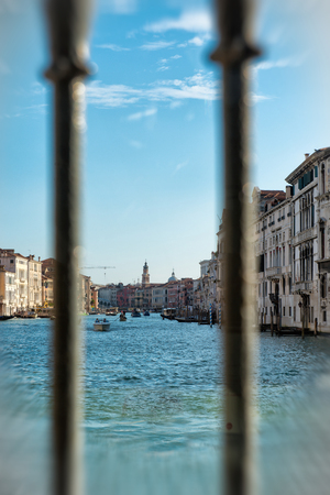 View through two upright metal railings of the Grand Canal, venice, Italy at low level showing the historic palaces and boat traffic on the water