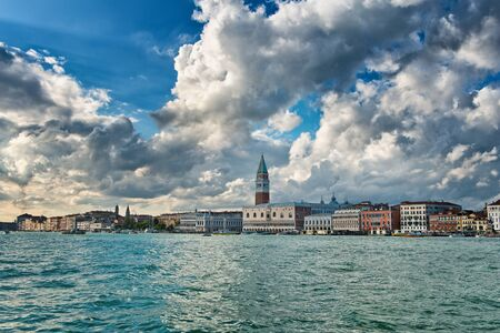 doges  palace: View from a boat of the Doges Palace and Campanile, Venice Italy with dramatic white clouds towering above in a travel and tourism concept