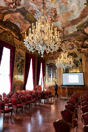 allegory painting: Interior of Aula Magna Silvio Trentin Room in Palazzo Dolfin - Ornate Room Decorated with Tiepolo Fresco Paintings, Elaborate Chandelier and Rows of Red Chairs Set Up for Conference Presentation Editorial