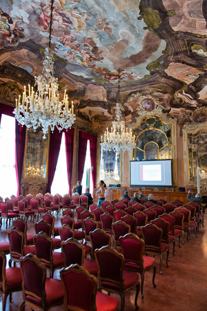 architectural studies: Interior of Aula Magna Silvio Trentin Room in Palazzo Dolfin - Ornate Room Decorated with Tiepolo Fresco Paintings, Elaborate Chandelier and Rows of Red Chairs Set Up for Conference Presentation Editorial
