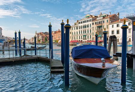 post: Water taxi moored alongside a wooden jetty and mooring posts on the Grand Canal, Venice, Italy with historic palaces visible behind Editorial