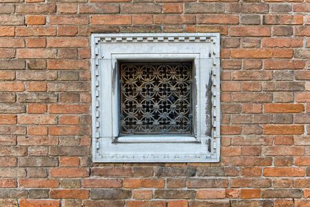 window frame: Square small window with white frame and decorative metallic grid on a brick wall of an old building, architectural detail