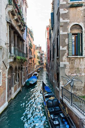 bordered: Scenic View of Gondola Boats Anchored Alongside Narrow Canal in Typical Street Scene Bordered by Traditional Colorful Architecture in Venice, Italy