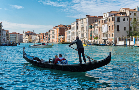 gondolier: Gondolier rowing tourists in his gondola on the Grand Canal in Venice past ancient historic palazzo with private boats in the background in a travel and tourism concept Editorial