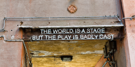 axiom: Quotation over a doorway entrance to a thoroughfare in Venice, Italy saying - The world is a stage but the play is badly cast