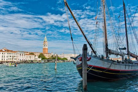 foreground focus: Focus on Masted Boat in Foreground with View of San Giorgio Island and Monastery Bell Tower in Background on Grand Canal Under Blue Sky, Venice, Italy Editorial