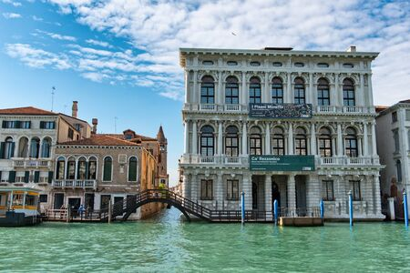 tourist destination: Historical palaces on the Grand Canal, Venice, Italy viewed across the water with a side canal and pedestrian bridge in this romantic tourist destination